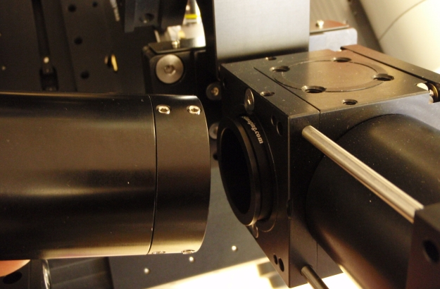 Tube lens assembly is attached to lower cubes on the microscope.