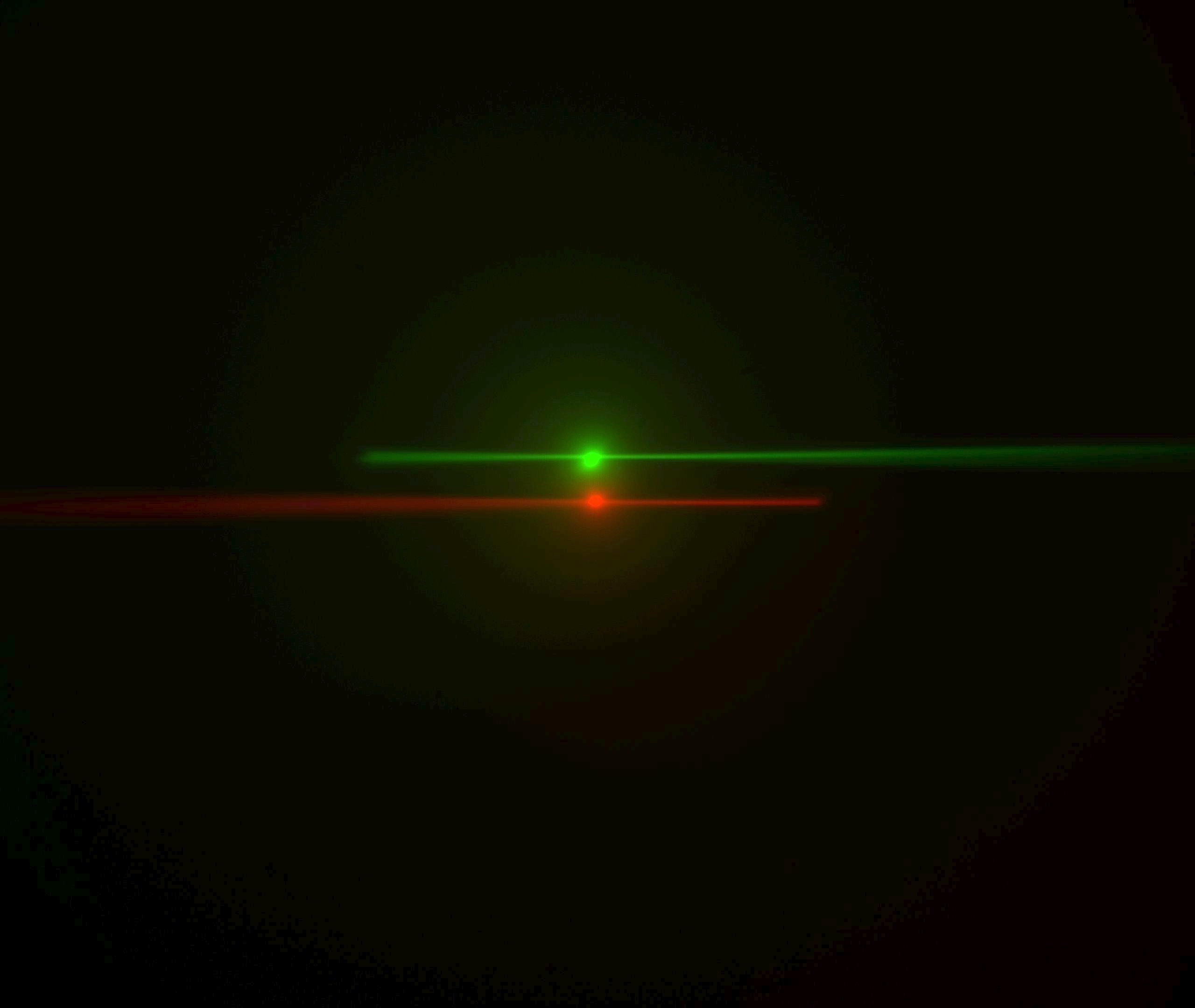Laser beams seen by cameras in conventional orientation. The green image is from the left-side camera and shows the beam from the right-side scanner entering from the right and eventually stiking the coverslip where it stops. The red image is from the right-side camera, shows the beam from the left-side scanner entering from the left. The bright spots are the epi-fluorescent excitation from the scanner on the same side as the respective cameras. The following statement will be understood after going though the alignment: the objective lateral alignment is perfect because the epi and beams exactly overlap, but the camera mirrors need to be adjusted slightly to put both epi spots in the image center.